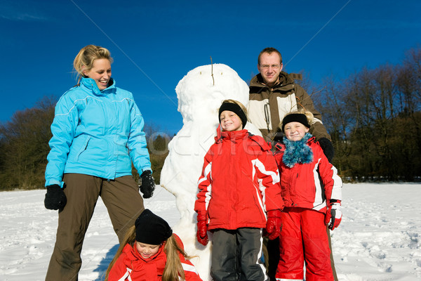 Family in winter standing in front of their snowman Stock photo © Kzenon