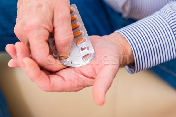 Senior medicate with pills at home Stock photo © Kzenon