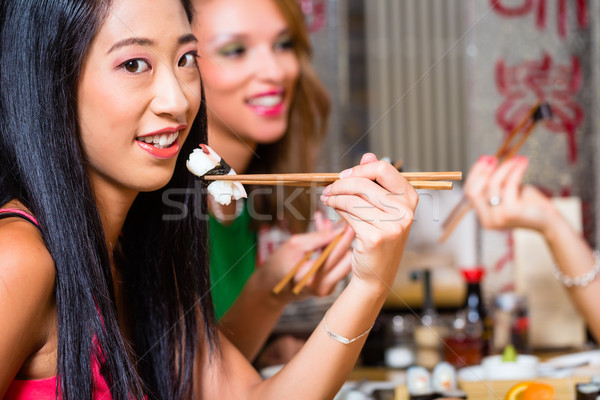 Jeunes manger sushis asian restaurant femme Photo stock © Kzenon