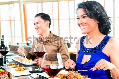 People in American diner with burger and wine Stock photo © Kzenon