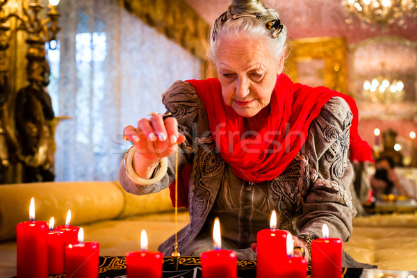 Soothsayer during a Seance or session with pendulum Stock photo © Kzenon