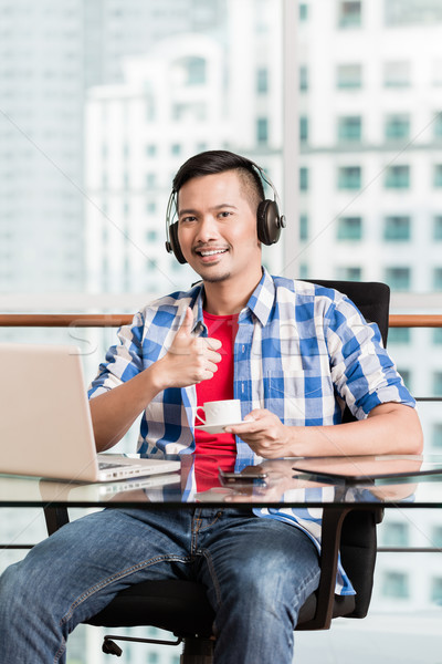 Young asian man in office having coffee giving thumbs up sign Stock photo © Kzenon