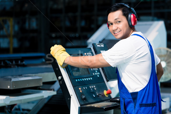 Worker entering data in CNC machine at factory floor to get the production going Stock photo © Kzenon