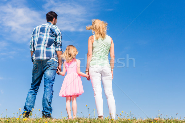Family standing with their backs to the camera in front of blue  Stock photo © Kzenon