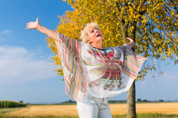 Active senior woman feeling free and happy while standing outdoo Stock photo © Kzenon