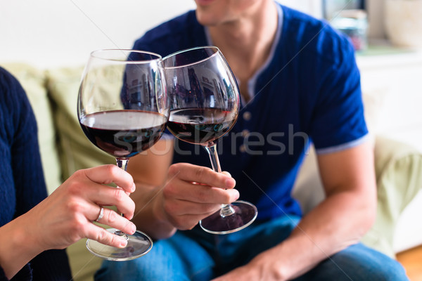 Romantic young couple toasting with red wine while sitting on th Stock photo © Kzenon
