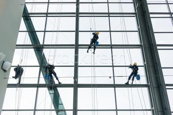 Professional window cleaners climbing up facade Stock photo © Kzenon
