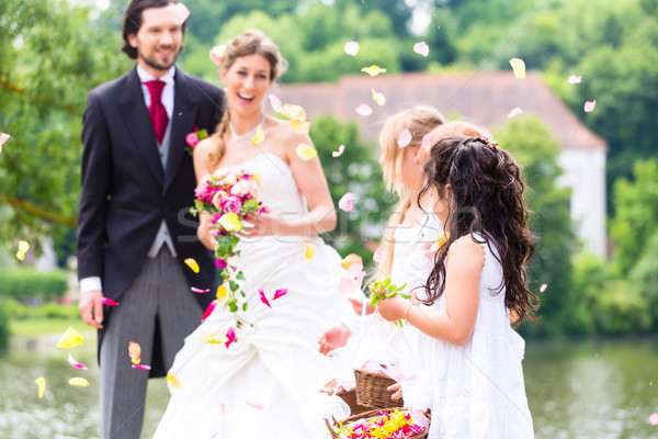 Stock photo: Wedding couple and bridesmaid showering flowers
