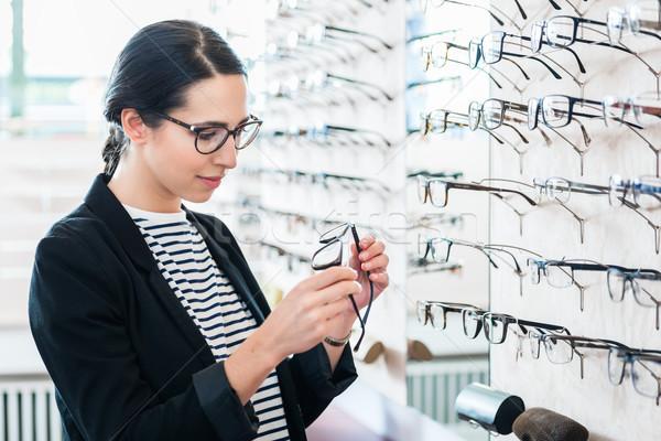 Woman taking glasses off shelf in optician shop Stock photo © Kzenon