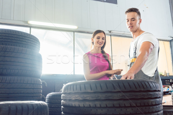 Handsome auto mechanic helping a customer to choose from various tires Stock photo © Kzenon
