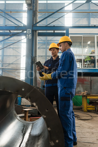 Experts checking information on tablet PC in a modern factory Stock photo © Kzenon