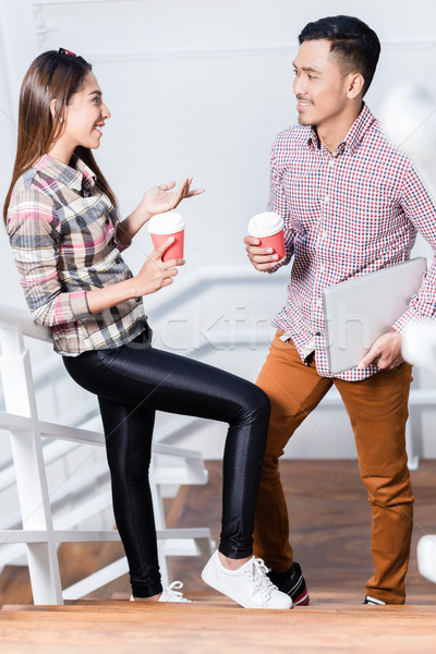 Young man and woman talking while drinking coffee during break at work Stock photo © Kzenon