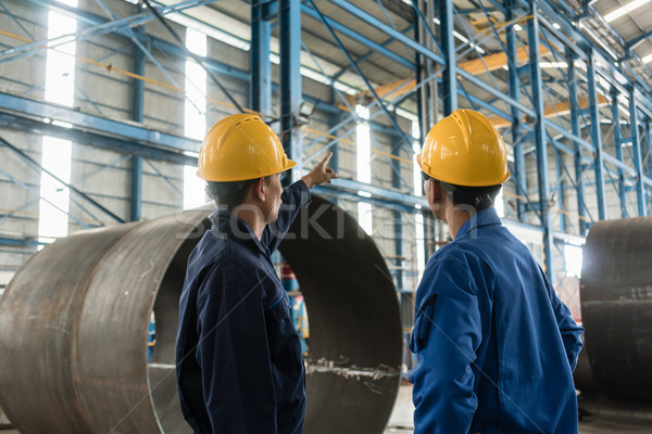 Skilled worker pointing up while giving instructions to an apprentice Stock photo © Kzenon