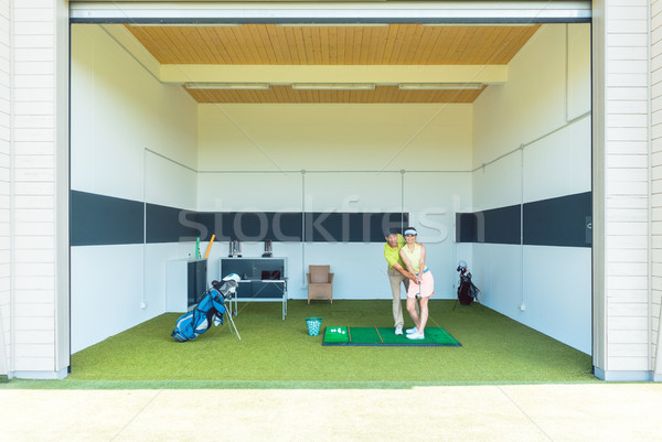 Dedicated golf coach using modern equipment while teaching a young woman Stock photo © Kzenon