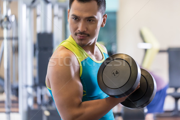 Portrait of a handsome young man exercising bicep curls at the gym Stock photo © Kzenon