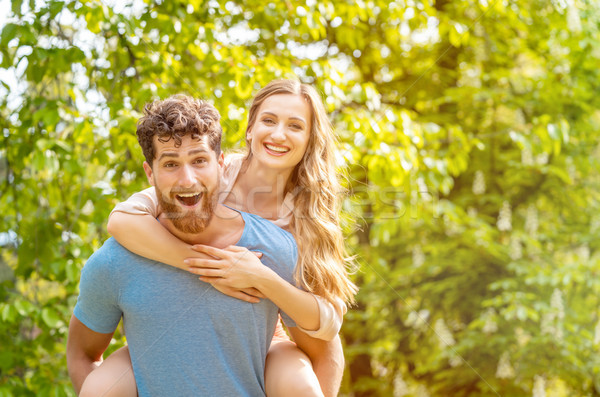 Husband is carrying his wife on his back being a reliable partne Stock photo © Kzenon