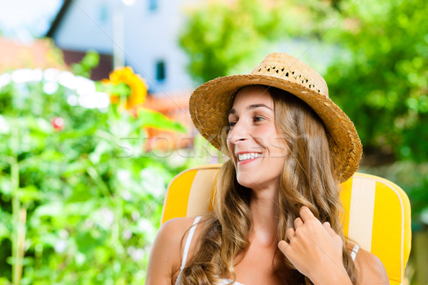 Woman tanning in her garden on lounge chair Stock photo © Kzenon