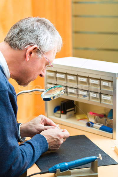 Acoustician working on a hearing aid Stock photo © Kzenon