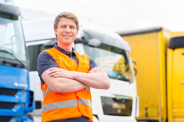 Forwarder or driver in front of trucks in depot Stock photo © Kzenon