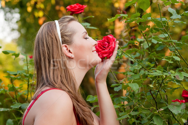 Woman in her garden sniffing at the roses Stock photo © Kzenon