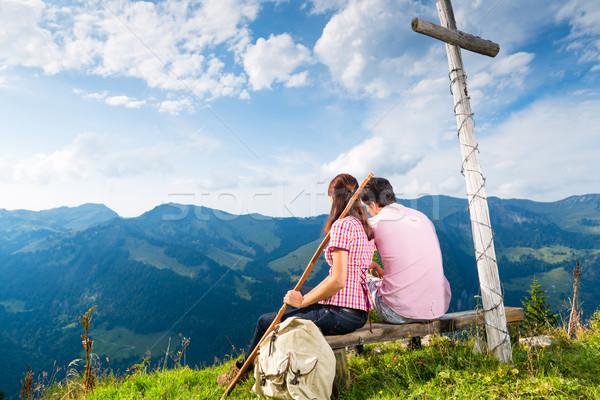 Alps - Hiking Couple takes break in mountains Stock photo © Kzenon