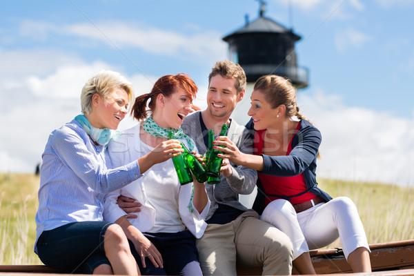 Friends drinking bottled beer at beach Stock photo © Kzenon