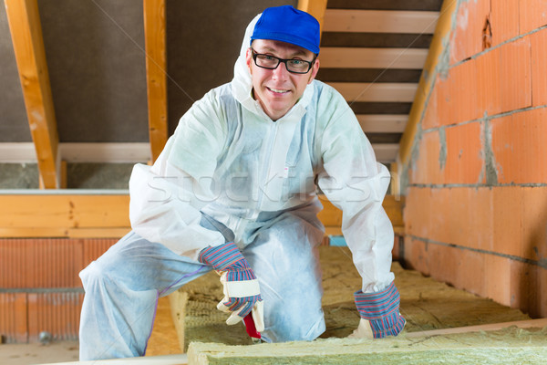 Stock photo: Worker cutting insulating material