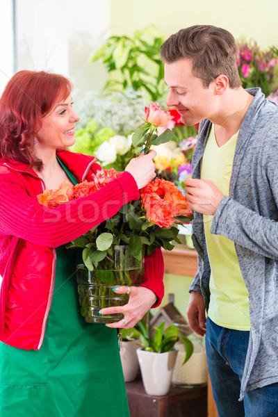 Costumer buying roses in flower shop Stock photo © Kzenon