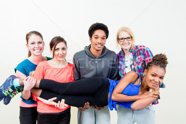 Friends in dance class carrying woman on hands Stock photo © Kzenon