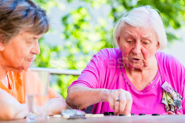 Two senior ladies playing board game in rest home Stock photo © Kzenon