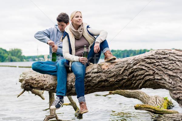 Man and woman sitting on trunk near  lakeside drinking beer Stock photo © Kzenon