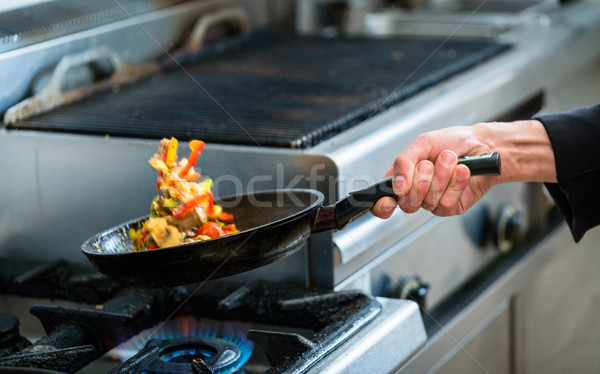 Chef is roasting vegetables in pan Stock photo © Kzenon