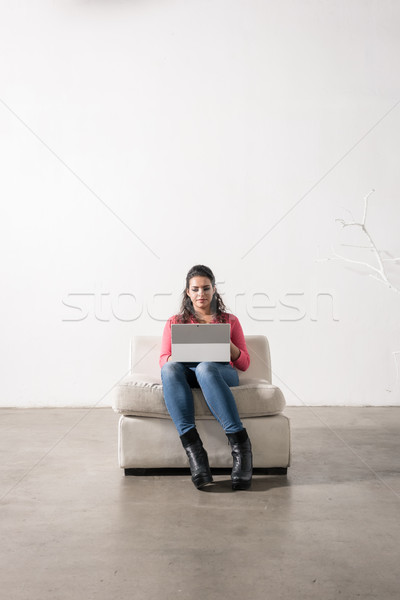 Young female freelancer sitting in armchair and working on noteb Stock photo © Kzenon