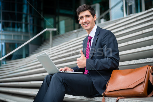 Successful young businessman showing thumb up outdoors Stock photo © Kzenon