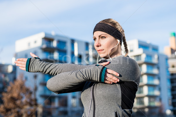 Portrait of a determined young woman stretching her left arm dur Stock photo © Kzenon