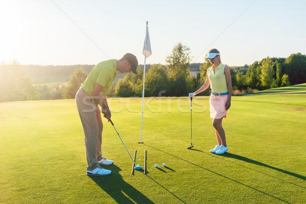 Man ready to hit the golf ball while exercising with his game pa Stock photo © Kzenon
