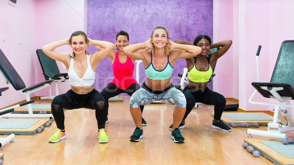 women doing squats during workout group class in modern health c Stock photo © Kzenon