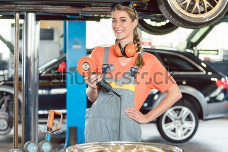 Portrait of a beautiful woman holding an impact wrench while wor Stock photo © Kzenon