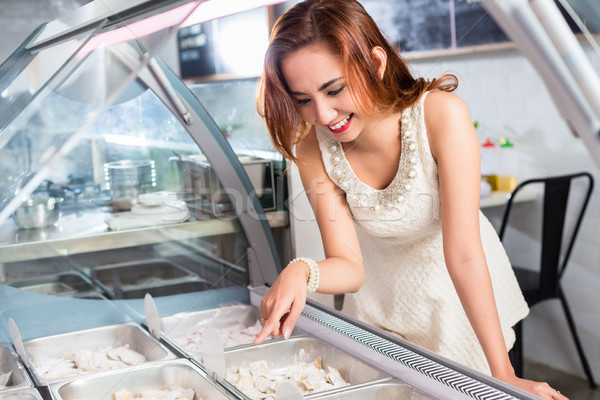 Smiling woman selecting food from a deli counter Stock photo © Kzenon