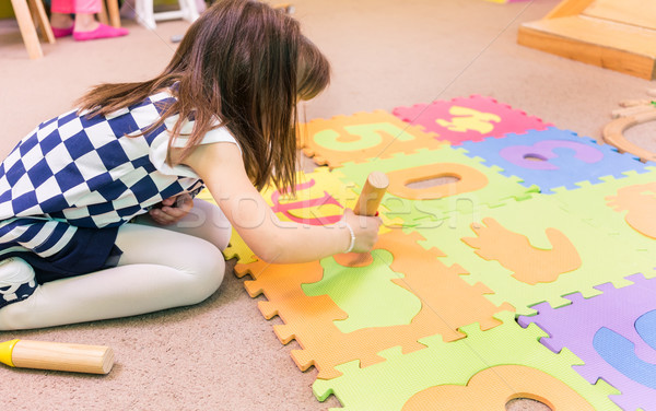 Cute pre-school girl playing with a colorful puzzle play mat Stock photo © Kzenon