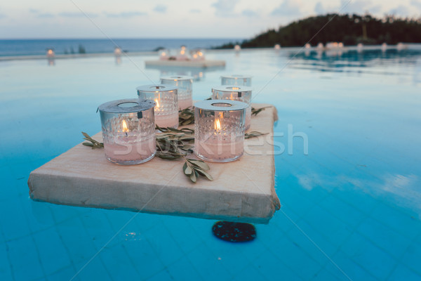 Candles floating in swimming pool at beach house party Stock photo © Kzenon