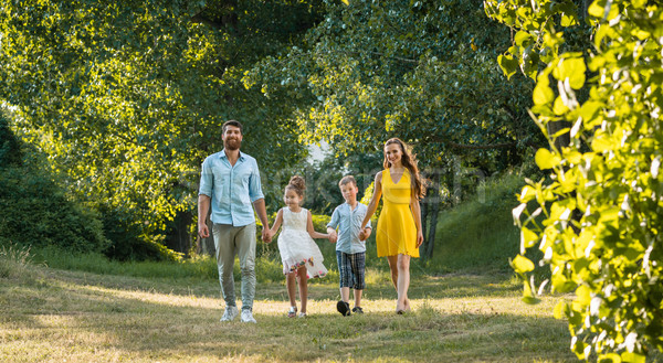 Happy family with two children holding hands during recreational walk Stock photo © Kzenon