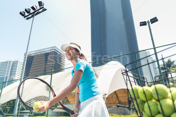 Cheerful beautiful woman playing tennis in a developed city Stock photo © Kzenon