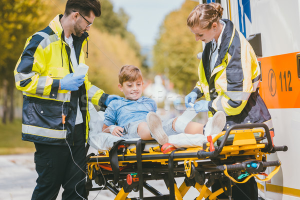 Medics putting injured boy on stretcher after accident Stock photo © Kzenon