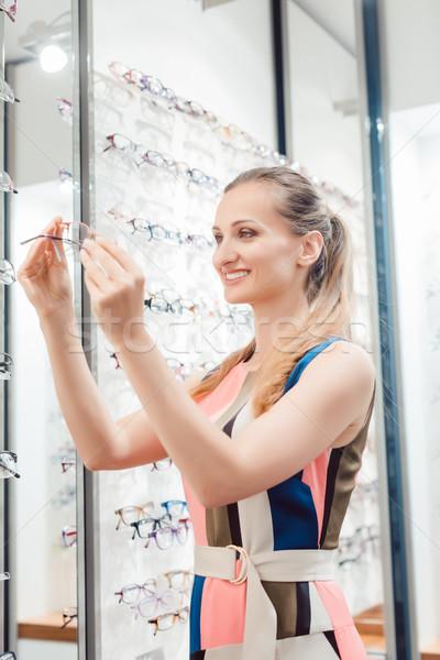 Beautiful woman choosing new glasses in store Stock photo © Kzenon