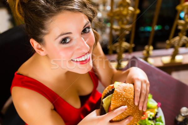 Young woman in fine restaurant, she eats a burger Stock photo © Kzenon