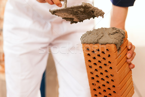 bricklayer making wall with brick and grout Stock photo © Kzenon