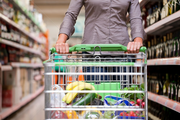 Young woman with pushcart in supermarket Stock photo © Kzenon