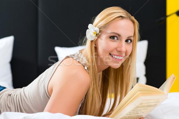 Genç kadın otel okuma kitap yatak otel odası Stok fotoğraf © Kzenon