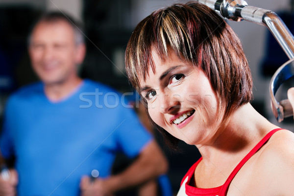 Mature woman exercising in gym Stock photo © Kzenon